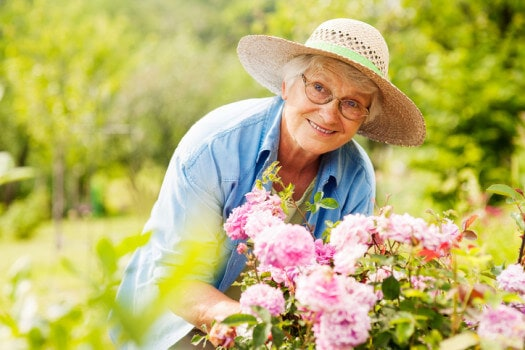 Senior woman with flowers in garden